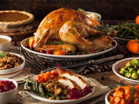 What protein source do scholars believe was featured at the very first Thanksgiving celebration?
