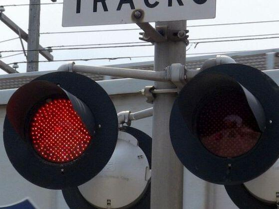 What does a flashing red light at a railroad crossing mean?