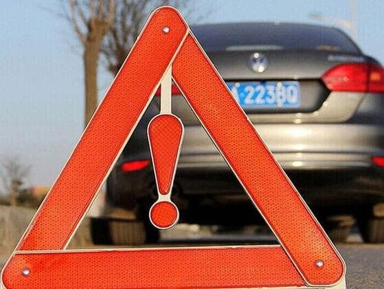 What does an orange triangle on the back of a vehicle indicate?