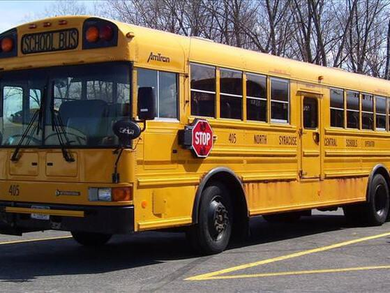 What must you do if a school bus has its lights flashing and its stop arm extended?