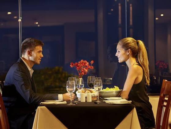 A couple sits at a restaurant. One of them is asking for the usual and the other is trying something new. Who is the first one?