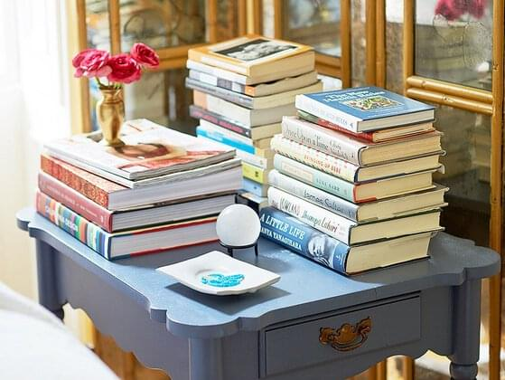 There are some books cluttered on the side table. How would you arrange them?