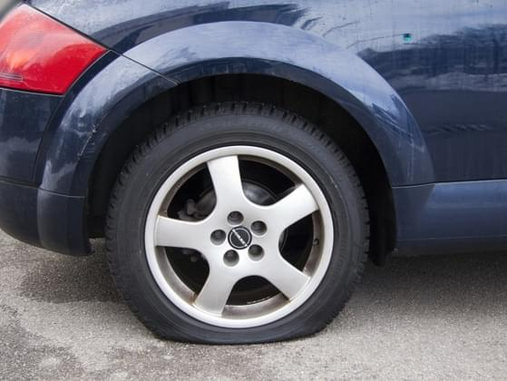 Driving to the store, you see your co-worker stranded on the side of the road with a flat tire. What do you do?