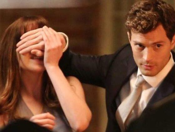 How many times does Christian whip Ana with a belt after she agrees to undergo total submission to him towards the end of the book?